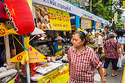 14 OCTOBER 2012 - BANGKOK, THAILAND:   A woman walks by food stalls during the Vegetarian Festival in Bangkok's Chinatown. The Vegetarian Festival is celebrated throughout Thailand. It is the Thai version of the The Nine Emperor Gods Festival, a nine-day Taoist celebration beginning on the eve of 9th lunar month of the Chinese calendar. During a period of nine days, those who are participating in the festival dress all in white and abstain from eating meat, poultry, seafood, and dairy products. Vendors and proprietors of restaurants indicate that vegetarian food is for sale at their establishments by putting a yellow flag out with Thai characters for meatless written on it in red.     PHOTO BY JACK KURTZ