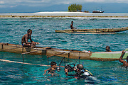 Local Papuan fisherman & Pete Oxford<br /> Half Island<br /> Cenderawasih Bay<br /> West Papua<br /> Indonesia<br /> Using spear and outrigger canoe