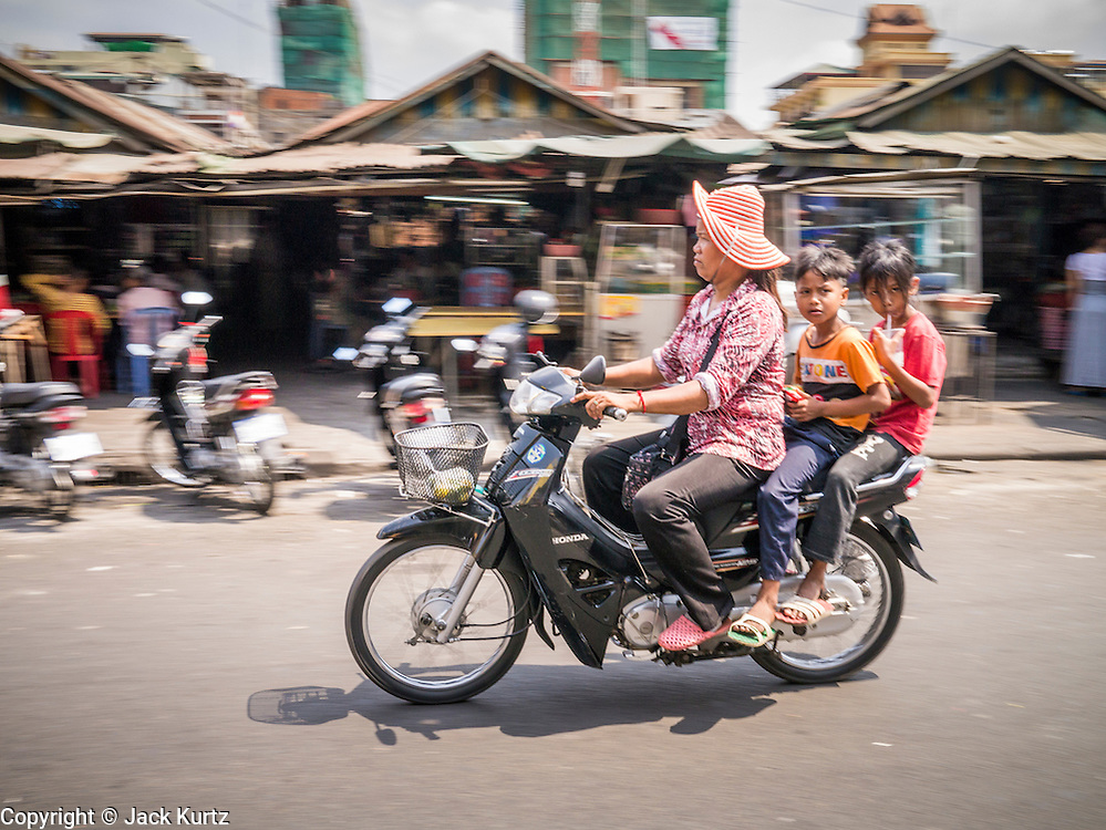 31 JANUARY 2013 - PHNOM PENH, CAMBODIA: A Cambodian family rides a motorcycle past a market in Phnom Penh. Motorcycles are frequently used for family transportation in Southeast Asia.  PHOTO BY JACK KURTZ