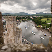 View of the river and boats from a tower at Caernarfon Castle in northwest Wales. A castle originally stood on the site dating back to the late 11th century, but in the late 13th century King Edward I commissioned a new structure that stands to this day. It has distinctive towers and is one of the best preserved of the series of castles Edward I commissioned.