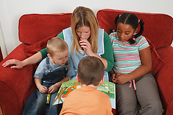 Nursery nurse reading book with children