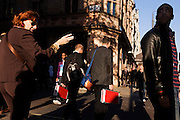 Two men carrying identical red cases walk along Piccadilly in late afternoon sunshine.