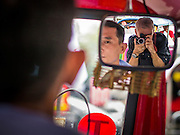 """10 DECEMBER 2012 - BANGKOK, THAILAND: Photojournalist JACK KURTZ photographs  a protest for constitutional reform from inside a """"tuk-tuk"""" (three wheeled taxi) on Ratchadamnoen Avenue in Bangkok Monday. The Thai government announced on Monday, which is Constitution Day in Thailand, that will speed up its campaign to write a new charter. December 10 marks passage of the first permanent constitution in 1932 and Thailand's transition from an absolute monarchy to a constitutional monarchy. Several thousand """"Red Shirts,"""" supporters of ousted and exiled Prime Minister Thaksin Shinawatra, motorcaded through the city, stopping at government offices and the offices of the Pheu Thai ruling party to present demands for a new charter.      PHOTO BY JACK KURTZ"""