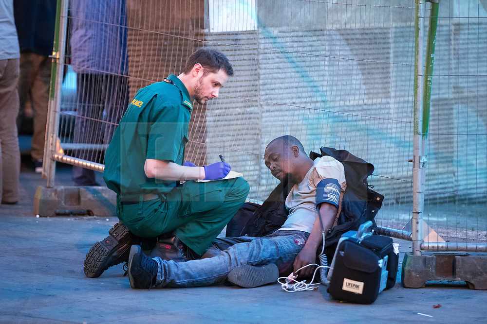 © Licensed to London News Pictures . 07/04/2017 . Manchester , UK . A paramedic tends to a man slumped on the ground in Piccadilly Gardens . Greater Manchester Police have authorised dispersal powers and say they will ban people from the city centre for 48 hours , this evening (7th April 2017) , in order to tackle alcohol and spice abuse . Photo credit : Joel Goodman/LNP