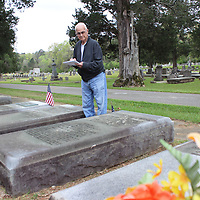 Clarence Brown takes notes between his parents' graves at Odd Fellows Cemetery. The 96-year-old is working on an ongoing inventory of all of the graves in the cemtery. The oldest one he's recorded dates back to 1806.