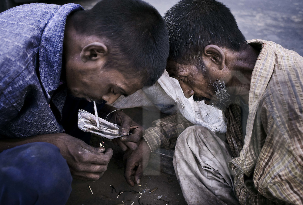 Two drug addicts smoke heroin in a street. Rajasthan, India, Asia