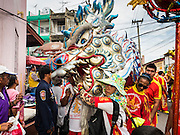 "23 JUNE 2015 - MAHACHAI, SAMUT SAKHON, THAILAND: Chinese dragon dancers perform during the City Pillar Shrine procession in Mahachai. The Chaopho Lak Mueang Procession (City Pillar Shrine Procession) is a religious festival that takes place in June in front of city hall in Mahachai. The ""Chaopho Lak Mueang"" is  placed on a fishing boat and taken across the Tha Chin River from Talat Maha Chai to Tha Chalom in the area of Wat Suwannaram and then paraded through the community before returning to the temple in Mahachai.   PHOTO BY JACK KURTZ"