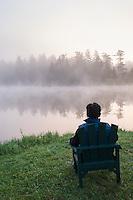 Man Sitting on Adirondack Chair at Dream Lake During Sunrise / Lakedale Resort Campground, San Juan Island, Washington