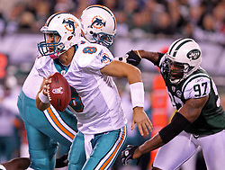 October 17, 2011; East Rutherford, NJ, USA; Miami Dolphins quarterback Matt Moore (8) eludes the pass rush from New York Jets linebacker Calvin Pace (97) during the first half at the New Meadowlands Stadium.