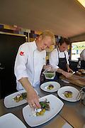 Kåseberga. Vendel Ales Stenar restaurant - Grill by the Sea. Owner/chef Anders Vendel (l.) preparing Fried herring with sour cream, lingonberries and new potatoes.