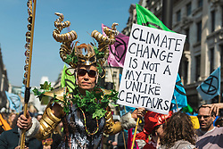 © Licensed to London News Pictures. 15/04/2019. London, UK. An environmental activist from the Extinction Rebellion movement in fancy dress as they block roads at Oxford Circus as part of a series of direct actions taking place across the capital. The protests demand urgent action from governments on climate change. Photo credit: Rob Pinney/LNP