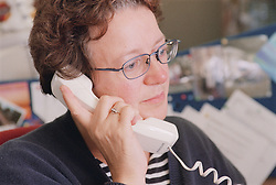 Woman working on Surviving Homelessness project using telephone in office,
