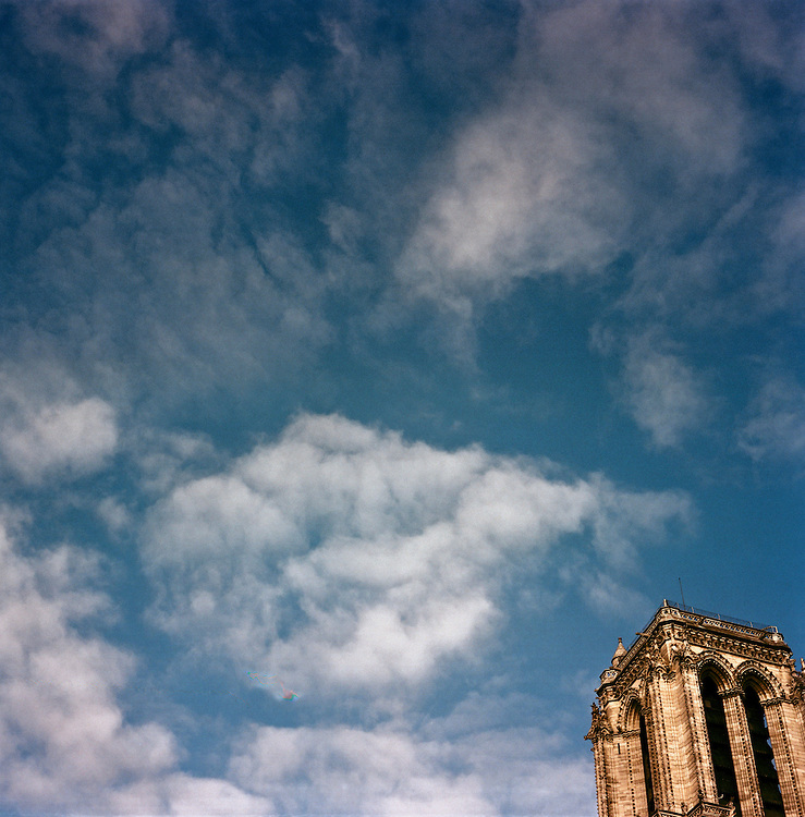 One tower of Notre Dame cathedral against blue sky with clouds, Paris