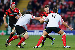 Saracens Outside Centre (#13) Joel Tomkins runs at Munster Number 8 (#8) James Coughlan (on his 100th Cap) and Lock (#4) Donncha O'Callaghan during the first half of the match - Photo mandatory by-line: Rogan Thomson/JMP - Tel: Mobile: 07966 386802 16/12/2012 - SPORT - RUGBY - Vicarage Road - Watford. Saracens v Munster Rugby - Heineken Cup Round 4.