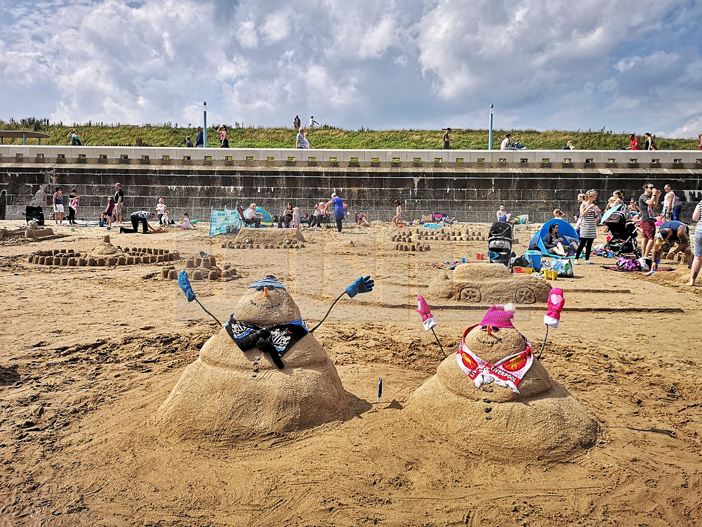 © Licensed to London News Pictures. 04/08/2019. Whitley Bay, UK. People take part in the Whitley Bay Sandcastle competition before the weather changes - with rain expected. Photo credit: Colin Scarr/LNP