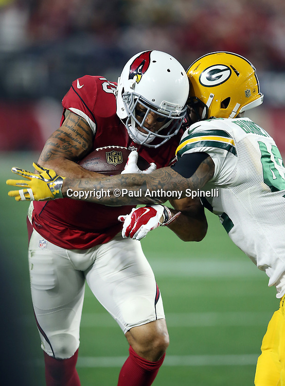 Arizona Cardinals wide receiver Michael Floyd (15) gets hit by Green Bay Packers strong safety Morgan Burnett (42) as he catches a fourth quarter pass for a 9 yard gain and a first down on a third down play during the NFL NFC Divisional round playoff football game against the Green Bay Packers on Saturday, Jan. 16, 2016 in Glendale, Ariz. The Cardinals won the game in overtime 26-20. (©Paul Anthony Spinelli)
