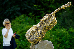 """© Licensed to London News Pictures. 03/07/2019. LONDON, UK. A woman views """"Celloswarm"""", 2002, by Bill Woodrow. Frieze Sculpture opens in Regent's Park, London's largest free display of outdoor art.  Works from 23 international artists are on display 3 July to 6 October 2019.  Photo credit: Stephen Chung/LNP"""