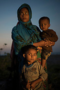 21 November 2017. Sawkat Ara (18), with children Mohammed Asim (2.3 months) & Umme Habiba (5). The group of Rohingya refugees arrived during the night by boat from Myanmar. Despite living for generations in Myanmar,  they are denied citizenship and widely considered to be illegal immigrants from Bangladesh. Cox's Bazar Region, Bangladesh. Photograph by David Dare Parker