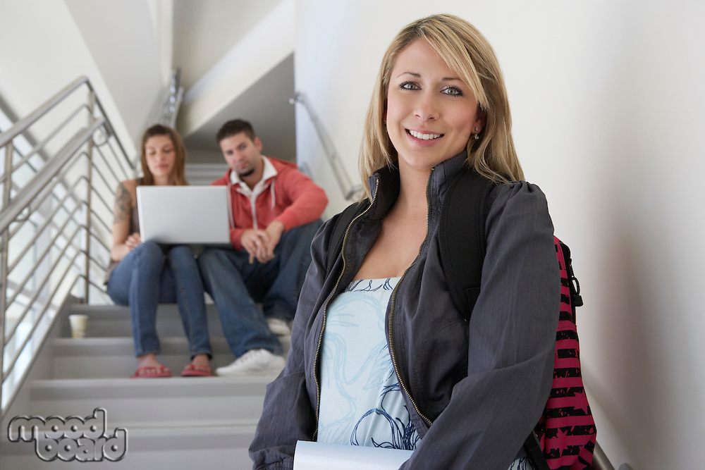 Portrait of female student on stairs, friends using laptop in background