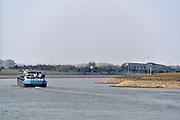 Nederland, Nijmegen,  21-10-2018Een binnenvaartschip vaart met containers die in nederland, rotterdam, op de Maasvlakte geladen zijn richting Ruhrgebied. Het schip kan slechts 20% van haar capaciteit benutten vanwege het lage water in de rijn. Laagterecord verbroken bij Lobith. De splitsing van de Rijn bij Pannerden in het Pannerdensch kanaal, wat uitkomt in de Nederrijn en de IJssel . Tweederde water naar de Waal, eenderde naar de aftakking. Rechts fort Pannerden .Foto: Flip Franssen