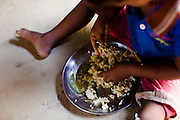 Pramila Tharu, 15, serves lentils and rice to her 2 year old toddler Prapti, in Bhaishahi village, Bardia, Western Nepal, on 29th June 2012. Pramila eloped and married at 12 and gave birth to Prapti at age 13. She delivered prematurely on the way to the hospital in an ox cart and her baby weighed only 1.5kg at birth. In Bardia, StC works with the district health office to build the capacity of female community health workers who are on the frontline of health service provision like ante-natal and post-natal care, especially in rural areas. Photo by Suzanne Lee for Save The Children UK