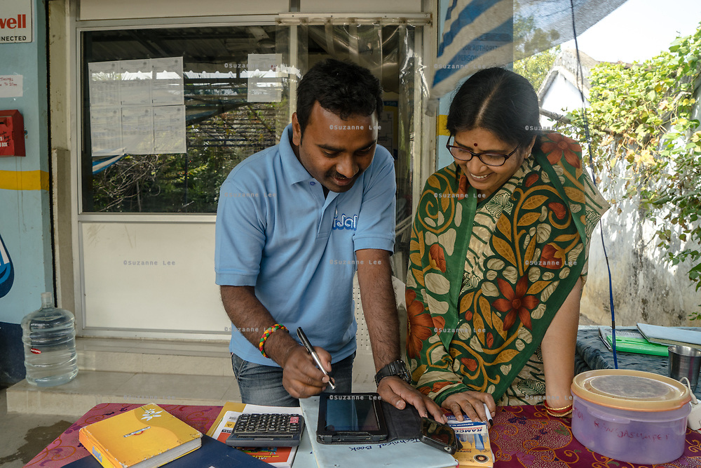 A Safe Water Network employee, left, speaks to Padmaja, the iJal station operator at the facility in Rangsaipet, in Waragal, Telangana, Indiia, on Saturday, February 9, 2019. Photographer: Suzanne Lee for Safe Water Network