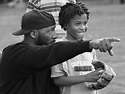 "Coach Rock works with player DeWan ""Puda"" Thompson as he pitches for the first time during a Newark Eagles Little League team practice at Weequahic Park."