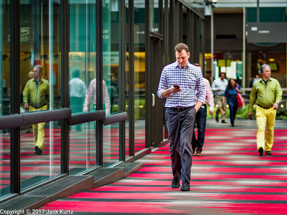 03 MAY 2017 - MINNEAPOLIS, MN:  People going into the IDS Center, the hub of the Minneapolis skyway system. The skyways are enclosed pedestrian overpasses that connect downtown buildings. The Minneapolis Skyway was started in the early 1960s as a response to covered shopping malls in the suburbs that were drawing shoppers out of the downtown area. The system grew sporadically until 1974, when the construction of the IDS Center and its center atrium, called the Crystal Court, served as a hub for the downtown skyway system. There are 8 miles of skyways, connecting most of the downtown buildings from Target Field (home of the Minnesota Twins) to US Bank Stadium (home of the Minnesota Vikings). In the last five years many upscale downtown apartment buildings and condominium developments have been added to the system, allowing downtown residents to live and work downtown without going outside.   PHOTO BY JACK KURTZ