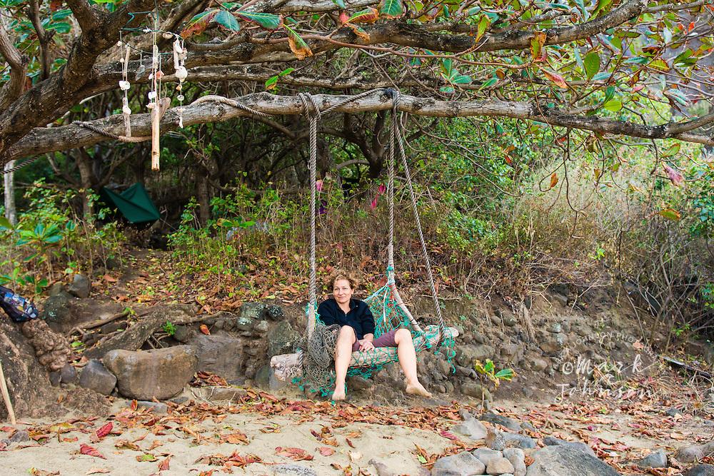Woman sitting in a rustic rope chair, Kalalau Beach, Na Pali Coast, Kauai, Hawaii
