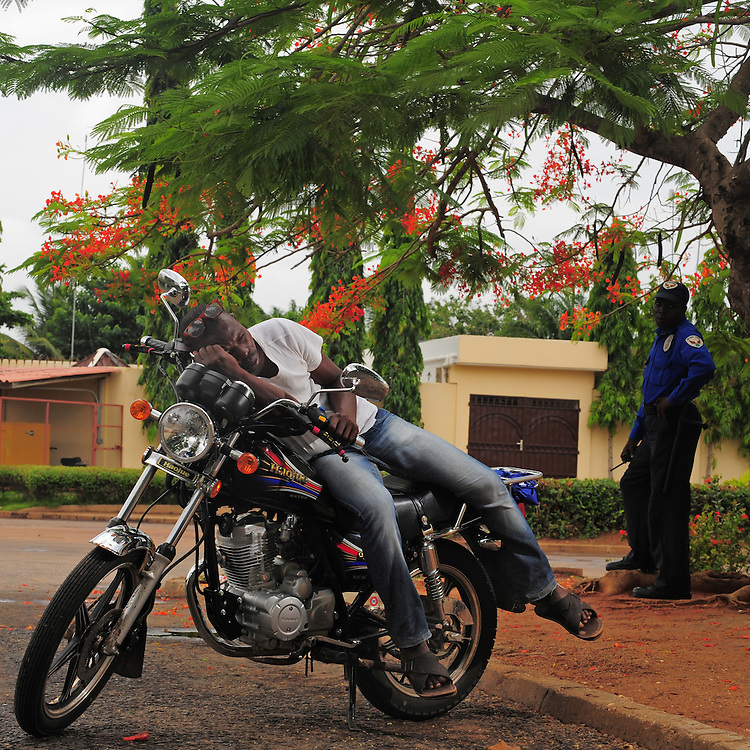 12-05-28   - LOME, TOGO -    Zemidjan ('take me quickly' in  Fon) driver Mohamed Dokouno demonstrates how he sleeps on his motorcycle in Lomé, Togo on May 28. Underpaid, rarely thanked and working all hours to make a meagre living, they find very few moments of calm and quiet in their lives. And so, the moto-taxi men have perfected various ways of calmly sleeping on their motorbike as they wait for  their next customer. And so, on the move amidst the chaos and bustle of daily life, they relax and sleep.  Photo by Daniel Hayduk
