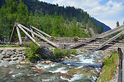 Aosta Valley/Italy-View of wooden bridge on alpine creek.