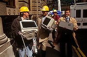 City workers carry office possessions including computer hard drives and files that were damaged by the IRA bomb that devastated the City of London's Bishopsgate area in 1993. Allowed to return to their desks to recover their data and working paperwork, they walk through the ancient streets en route to new emergency office elsewhere in the capital. The Irish Republican Army (IRA) exploded a truck bomb on Bishopsgate. Buildings up to 500 metres away were damaged with one and a half million square feet (140,000 m) of office space being affected and over 500 tonnes of glass broken. Repair costs reached approx £350 million. It was said that Roman remains could be viewed at the bottom of the pit the bomb created. One person was killed when the one ton fertiliser bomb detonated directly outside the medieval St Ethelburga's church.