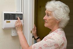 Woman setting house alarm system,