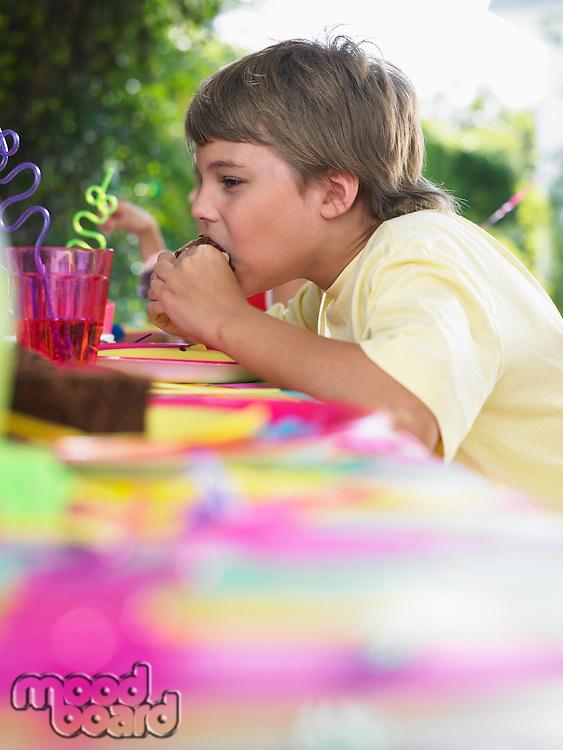 Young boy (10-12) eating cupcake at birthday party