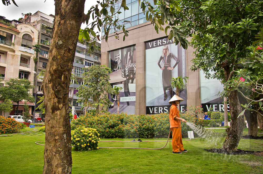 Vietnamese woman sprinkles water around a tree in a park. Luxury mall in background. Ho Chi Minh city (HCMC), Vietnam, Asia