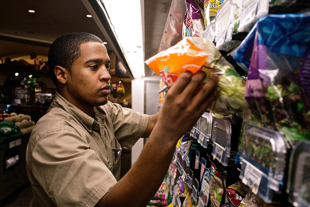 Elio Perdomo, restocks lettuce in the produce section at a Safeway grocery store in Silver Sping, MD. Perdomo, a student at Montgomery College, tries to take classes in the morning and works up to 16 hours a week at the supermarket.