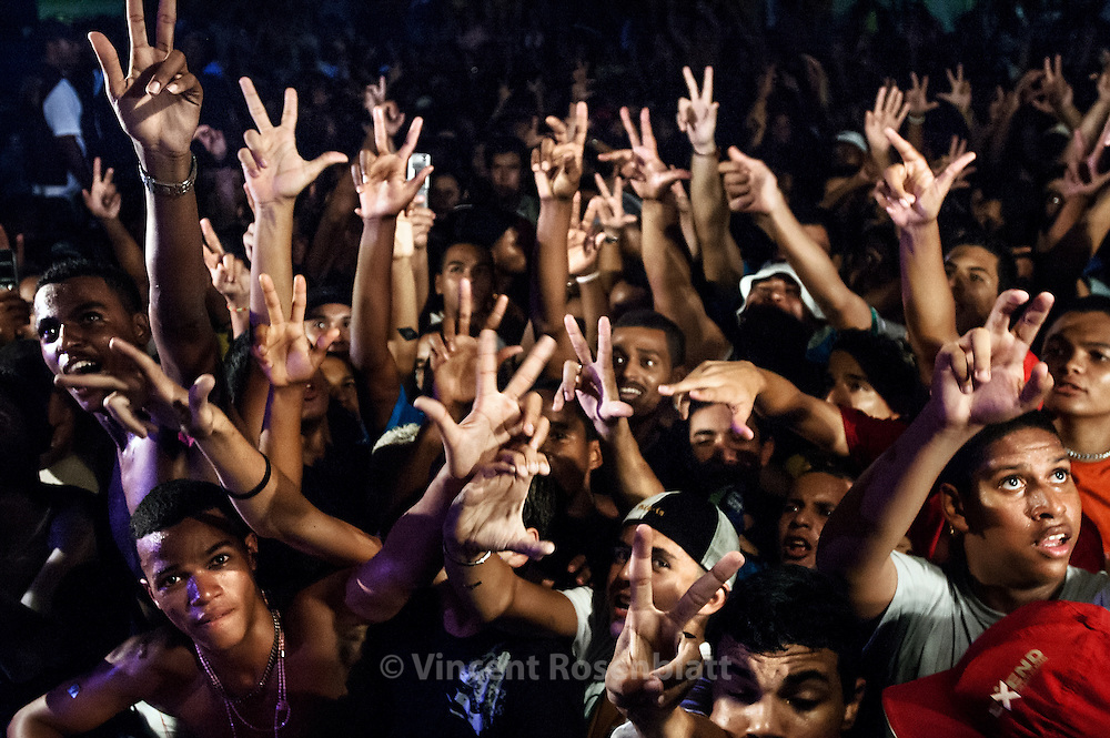 """Baile"" of Furacão Tsunami, the most powerful soundsystem on the Funk scene in Rio. Club Boqueirão, downtown Rio de Janeiro . Every hand gesture has a meaning : 3 fingers apart mean ""Vida louca"" (crazy life), the C and V letters symbolize the Commando Vermelho, the principal drug faction in Rio's favelas."