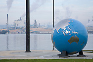 Globe sculpture in waterfront park of Commencement Bay, Tacoma Washington with Simpson Lumber Mill in background