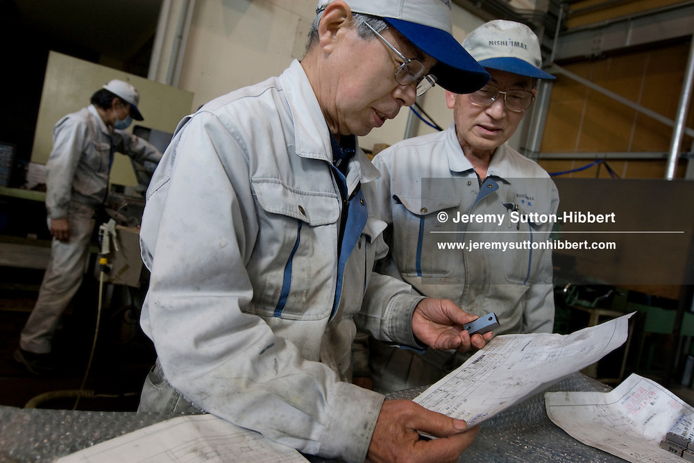 Katsuya Hyodo (74 years old, centre of pic) at work, with colleague Takayoshi Hirao (75 years old, right of pic), in Nishijimax Corp, Toyokawa, Japan. Nishijimax Corporation does not have a retirement age limit for it's employees, they can retire when they feel it is time. Out of the present workforce of 150 employees, 18 are over the age of 60, with three employees having worked for the company for more than 50 years, including Katsuya Hyodo.