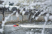 Nick Troutman kayaking in a rare Reno spring snowstorm at the whitewater park in downtown Reno, Nevada.