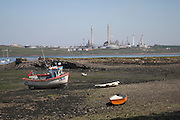 Fishing boats on Angle beach contrast with Chevron oil refinery, Pembroke, Pembrokeshire Wales