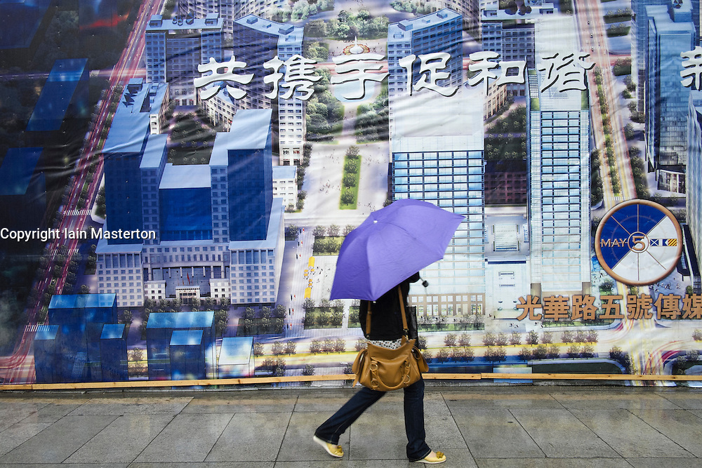Woman walks past billboard showing planned future layout of Central Business District CBD in Beijing China