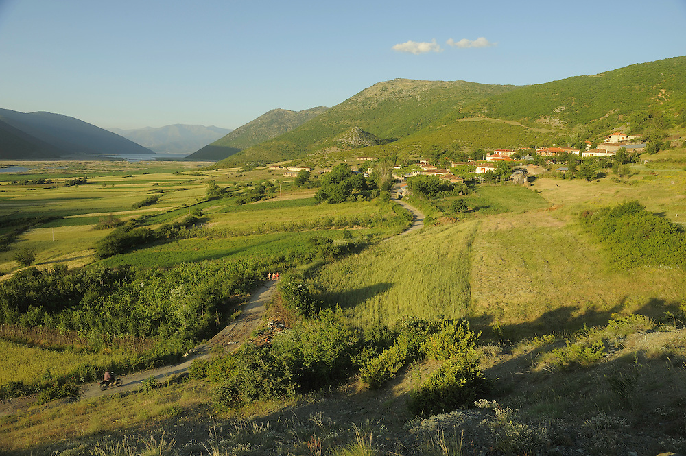 Village with Lesser Lake Prespa in the background. Lake Prespa National Park, Albania June 2009