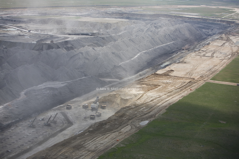 Trucks carrying off extracted coal in the Powder River Basin. The Powder River Basin is a geological structural basin in southeast Montana and northeast Wyoming. This region supports about 40 percent of the United States coal supplies. Therefore, there is strip mining being done in this area. Strip mining is a type of surface mining that involves excavating earth and rock to uncover a layered mineral reserve. The excavation of the overburden (overlying material) is completed in rectangular blocks in pits or strips.