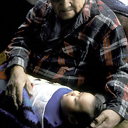 Zuni, Native Americans - two generations - grandfather holding infant grandson in cradle board, Zuni Pueblo, NM