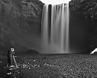 Black and White with one Color. Skogarfoss, a Waterfall in Southern Iceland. Only another photographer setting up his image (and his very patient wife in red at the base of the waterfall) would be still enough for a 10 second exposure. Image taken with a Nikon Df camera and 24 mm f/1.4G lens + 10 stop Singh-Ray Neutral density filter (ISO 800, 24 mm, f/8, 10 sec).