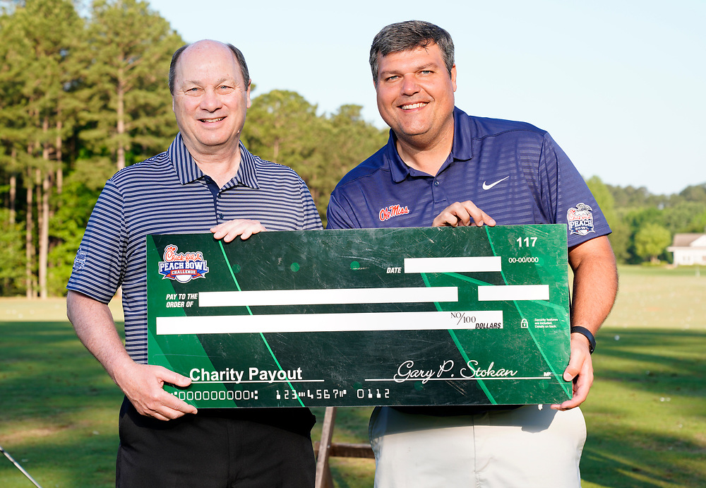 Peach Bowl, Inc. CEO & President Gary Stokan presents Ole Miss head football coach Matt Luke a check for his charity after the Chick-fil-A Peach Bowl Challenge at the Ritz Carlton Reynolds, Lake Oconee, on Tuesday, April 30, 2019, in Greensboro, GA. (Paul Abell via Abell Images for Chick-fil-A Peach Bowl Challenge)