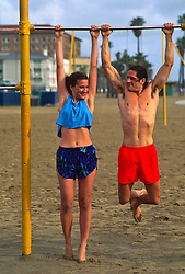Couple doing pull ups at the Santa Monica beach workout area