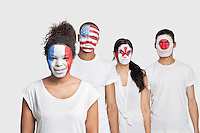Portrait of Multi-ethnic group of friends with various national flags painted on their faces standing against white background