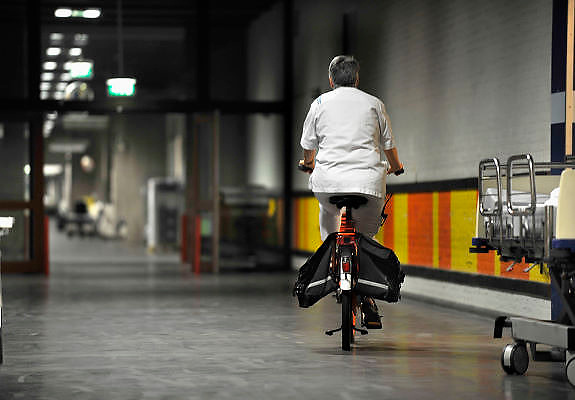 Nederland, Nijmegen, 7-9-2011Verpleegkundige fietst in de nacht door een gang van hetziekenhuis UMC Radboud. Nachtdienst, veiligheid, angst, gevoel van onveiligheid, donker, onzeker, openbaar gebouw, diefstal, criminaliteit.Foto: Flip Franssen